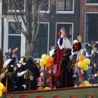 Sinterklaas and Zwarte Pieten waving to the crowds along the Amstel river in Amsterdam