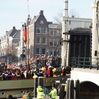Sinterklaas waving to the crowd as his steamboat passes through the Magerebrug
