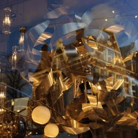 Houses are reflected in a lamp shop window