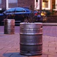 Kegs re-purposed as planters in front of an important brown cafe.