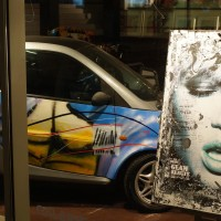 Smart car and painting in a gallery next door.
