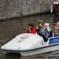 American girls looking fabulous, putting on makeup while navigating through the tourboats in a peddle boat.