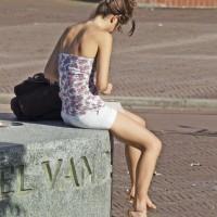 Pretty girl taking a break on a statue