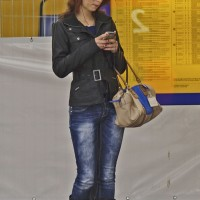 Beautiful girl waiting for the train and texting